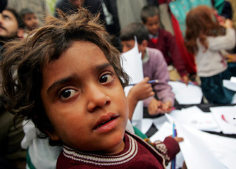 A young survivor of last week's deadly Pakistan earthquake looks on as children draw during a workshop held in Muzaffarabad