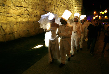 Israeli performers wear illuminated costumes as they perform during the Jerusalem Festival of Lights in Jerusalem's Old City
