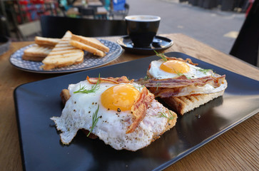 fried eggs with crispy bacon on toast