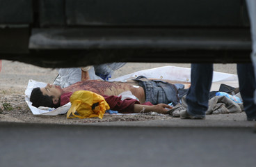 The body of a Palestinian man lies on a road near the Jewish settlement of Eli