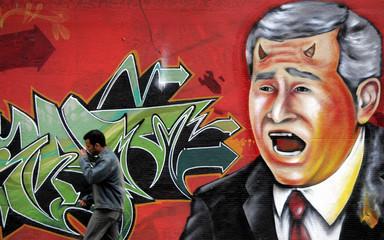 A man walks past a mural depicting U.S. Bush with devil horns in Rio de Janeiro.