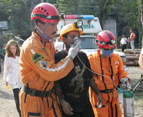 Colombian rescue workers attend a miner at the entrance of a coal mine that exploded in Sardinata