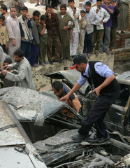 Iraqi policeman searches through destroyed vehicles following powerful car bomb in holy Iraqi city of Najaf
