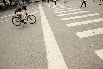 A cyclist waits for pedestrians to cross a zebra crossing in Beijing