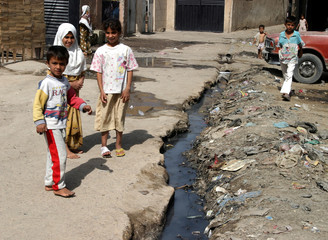 Young Iraqis stand next to an open sewer canal on a Baghdad street, May 11, 2003.[One month after th..