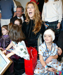 Canadian  pop diva Celine Dion winks as she has her picture taken with sick children at Sainte-Justi..