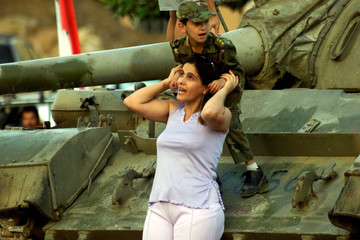 A LEBANESE CHILD HELD BY HIS MOTHER CLIMBS ABROAD A T-55 TANK.