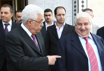 Palestinian President Abbas walks with Syria's Foreign Minister al-Moualem in Damascus