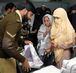 A Pakistani army personal checks the bags of Muslim women at Multan's airport.