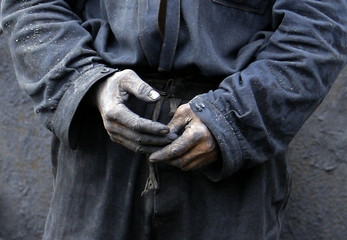 A coalminer hands are seen as he rests after emptying his trolley of coal at a small mine in Qianjiangping village in Heibei Province near the town of Badong in the south-west part of China