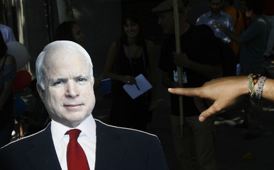 "A member of the ""Spain for McCain"" platform points at a cardboard standee of U.S. Republican presidential candidate McCain in Madrid"