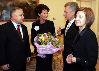Polish President Aleksander Kwasniewski and his wife Jolanta talk to President elect Lech Kaczynski and his wife Maria in the Presidential palace in Warsaw