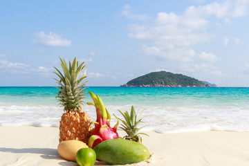 Tropical fruits on the sandy beach against the turquoise sea. Similan Islands, Thailand Wall mural