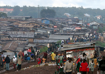 Kenyans walk along a railroad as they go to work early in the morning in Nairobi's Kibera slum.