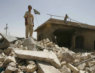 A boy stands amid the rubble of the destroyed Al-Ashra Sunni mosque after a bomb attack in Basra