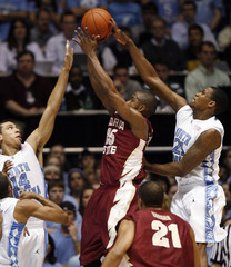 The University of North Carolina's Danny Green and Deon Thompson defend Florida State University's Jason Rich in NCAA basketball from Chapel Hill