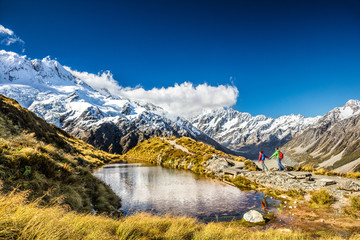 Hiking travel nature hikers in New Zealand. Couple people walking on Sealy Tarns hike trail route with Mount Cook landscape, famous tourist attraction.