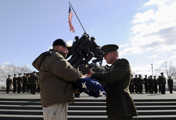 US Marine Corps veteran receives a flag in honor of the 64th anniversary of the raising of the US flag on the island of Iwo Jima during World War II, during a ceremony at the Marine Corps War Memorial in Arlington, Virginia