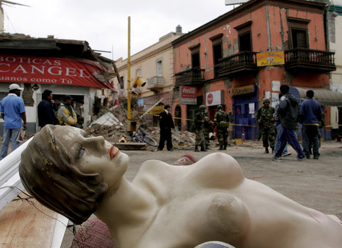 A mannequin is seen lying on the floor as people remove their belongings from a shopping center in the main plaza in Pisco
