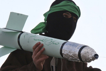 Islamic Action Front supporter holds toy rocket during rally in Amman