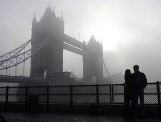 A couple are silhouetted in front of Tower Bridge during foggy conditions in London