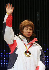 Ahn of South Korea celebrates after receiving his medal for the men's 1500 metres short track speed skating event in Turin