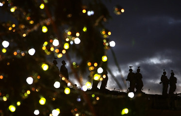 Statues on the colonnade in St. Peter's Square are seen in the background as a Christmas tree is officially lit at the Vatican