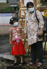 A mother and child wait for transport after getting her daughter tested for suspected H1N1 influenza in Mumbai