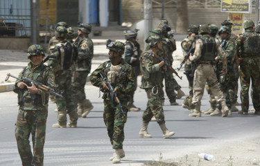 U.S. and Iraqi soldiers secure the area after an attempted attack on an Iraqi army convoy in Baghdad
