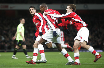 Arsenal's Jay Simpson celebrates his goal against Wigan Athletic with team mates Fran Merida and Jack Wilshere during their Carling Cup soccer match at the Emirates Stadium in London