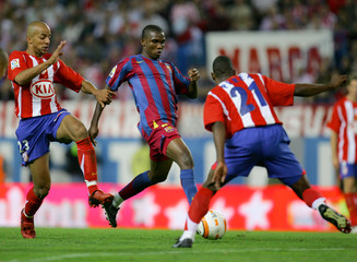 Barcelona's Eto'o dribbles against Atletico Madrid's Luccin and Perea during Spanish first division ...