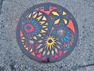 A manhole cover of Matsumoto city, Nagano Prefecture, Japan. Temari balls engraved on a manhole cover. Matsumoto-temari are folkcraft balls decorated with yarn.