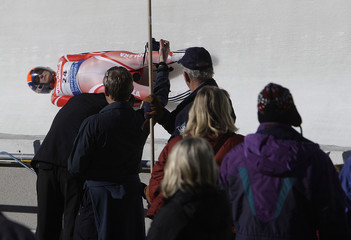 Spectators watch and take pictures as Poland's Ewelina Staszulonek competes in the Luge World Cup in Whistler