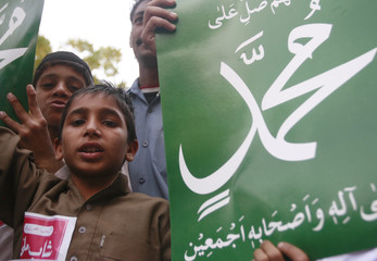 A boy holds a placard during a protest against the republication of Prophet Mohammad's caricature in Karachi