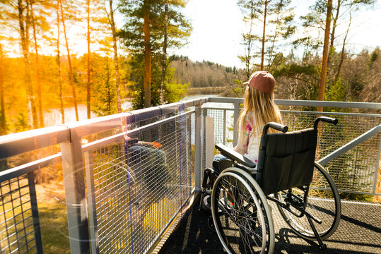 Young girl in a wheelchair on a balcony looking at the nature in the spring
