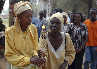 Rwandan genocide survivors relay a symbolic torch in front of a mass grave in Kigali