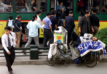 A POOR CHINESE MAN SLEEPS ON A THREE WHEELED FLAT-BED BICYCLE INBEIJING.