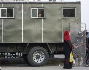 Women walk past police trucks and riot police in a main square in Mahalla al-Kobra