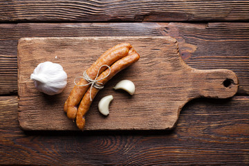 Raw sausage and garlic on wooden table