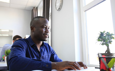 Handsome Afro American businessman working in office.