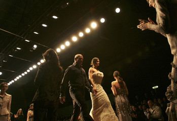 Manuela Arcuri, an Italian TV star and Luciano Soprani acknowledge the applause at the end of Soprani's Fall/Winter 2006/07 women's collections during Milan's fashion week February