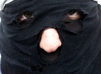 Masked Jordanian of Palestinian origin faces Jordanian riot police blocking the road to King Hussein..