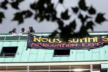 Protesters adjust a banner on top of French employers group MEDEF headquarters in Paris, June 25, 20..