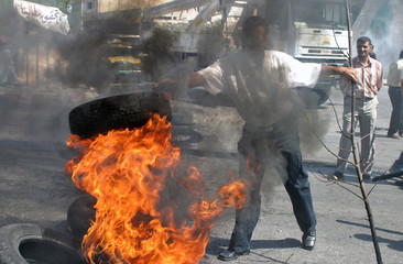Palestinian government employees burn tyres and block the main intersection during a protest for their unpaid salaries in Bethlehem