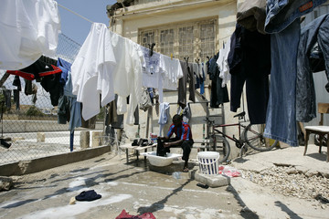 African immigrant washes clothes at the open centre for migrants in Marsa, in Valletta's Grand Harbour