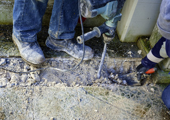 Workers perform small excavation work with tools during new fiber optic construction work. closeup with blurred motion