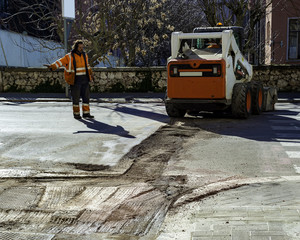 Worker watches the movement of a bobcat during street maintenance work