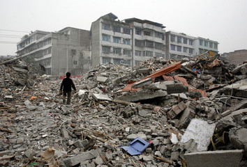 A former resident of a collapsed apartment block walks over the rubble as she searches for her belongings in the earthquake-devastated city of Dujiangyan