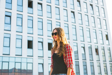 Summer sunny lifestyle fashion portrait of young stylish hipster woman walking on the street, wearing cute trendy outfit, smiling enjoy her weekends