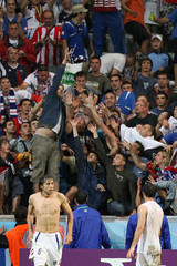 Fans reach for the shirt of Serbia and Montenegro's Goran Gavrancic at the end of their Group C World Cup 2006 soccer match against Ivory Coast in Munich